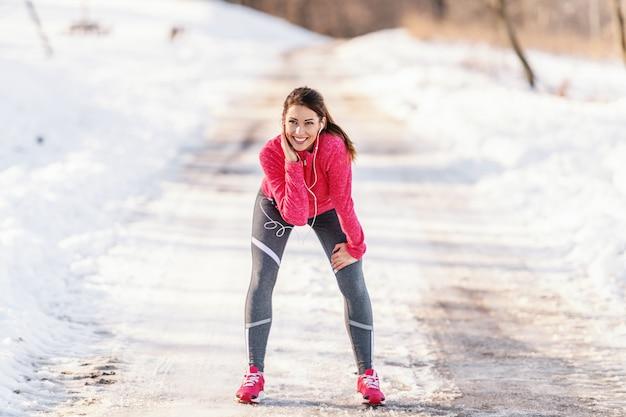 スポーツウェアとポニーテールで休んでいると膝に手を握って音楽を聴く若い美しいブルネット。冬のフィットネスの概念。