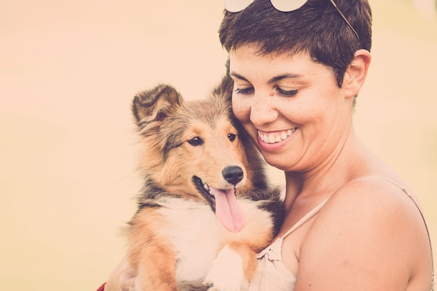 Young beautiful brunette lady with freckles hug a beautiful puppy pet shetland dog - smile and happiness concept for alternative couple in love and best friend