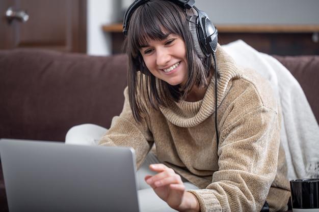 Молодая красивая брюнетка улыбается в уютном свитере и смотрит на экран ноутбука. концепция онлайн-обучения, удаленной работы, видеосвязи.