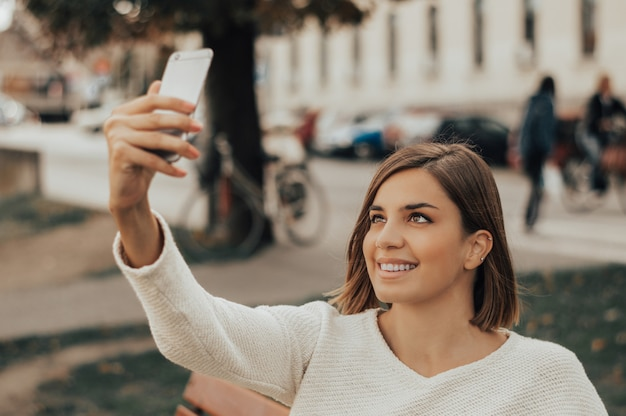 Young beautiful brunette taking pictures of herself on a cellphone in a city park.