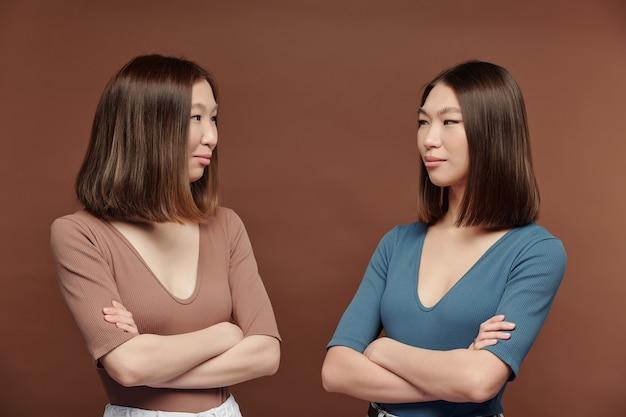 スタジオで茶色の背景に対してカメラの前でお互いを見ているカジュアルなプルオーバーの若い美しいブルネットの双子の姉妹