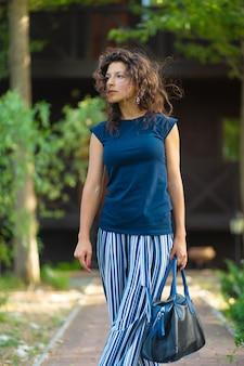 가방 세련 된 옷에 곱슬 머리를 가진 젊은 아름 다운 갈색 머리. 녹색 공원에서 밝은 여름날 즐기기.