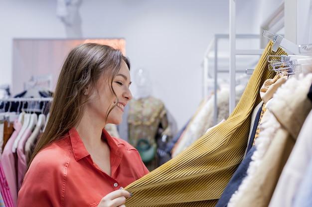 Молодая красивая брюнетка женщина покупает юбку в торговом центре сезонные распродажи, концепция покупок в черную пятницу