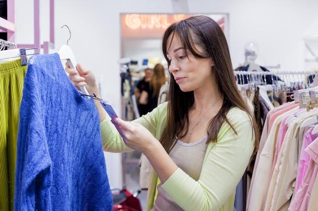Молодая красивая брюнетка женщина покупает свитер в торговом центре сезонные распродажи, концепция покупок в черную пятницу