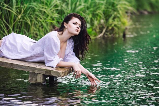 若い美しいブルネットの女性はターコイズブルーの澄んだ水で湖を楽しんでいます