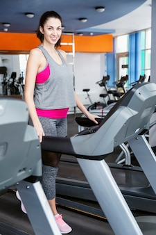 Young beautiful brunette woman at the gym in the cardio zone. vertical.