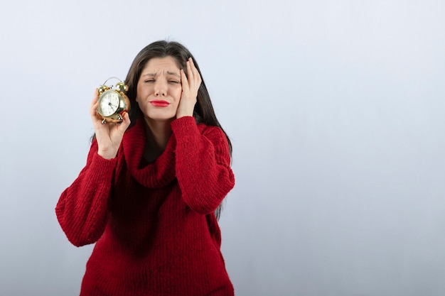 Young beautiful brunette woman holding an alarm clock standing over white background