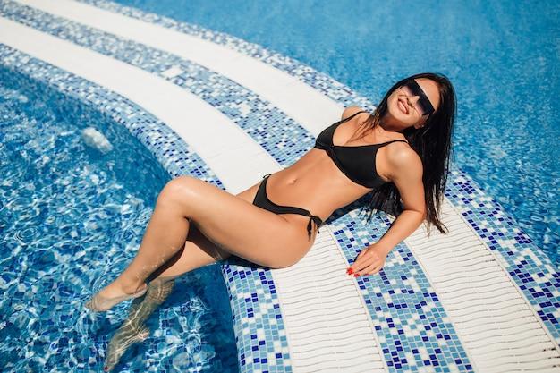 Молодая красивая брюнетка в черном купальнике, солнцезащитных очках, лежа и загорать в бассейне у воды