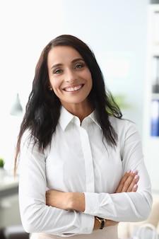 オフィスの肖像画に笑みを浮かべてビジネススーツの若い美しいブルネットの女性。実業家の成功達成コンセプト。