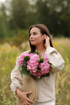 Young beautiful brunette woman is holding bouquet of pink flowers hydrangea in a straw bag,