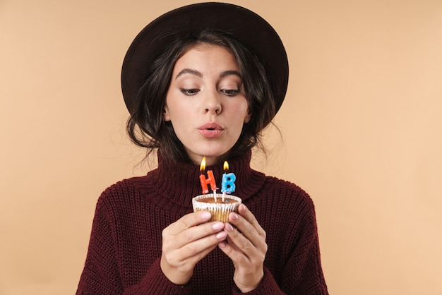 Young beautiful brunette woman isolated over beige wall wall holding cupcake blowing out happy birthday candles.