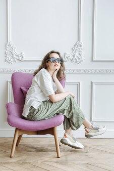 새로운 유행의 옷을 입고 레슬링에 앉아 있는 동안 스튜디오에서 포즈를 취하는 젊고 아름다운 브루네트 여성 모델