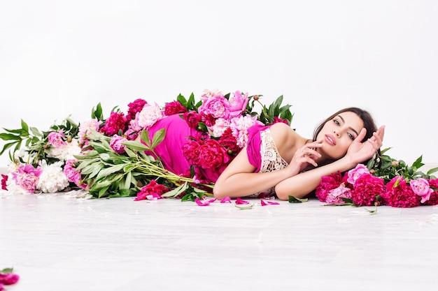 아름 다운 메이크업과 핑크 색상 모란에 긴 머리를 가진 젊은 아름 다운 갈색 머리 여자 모델