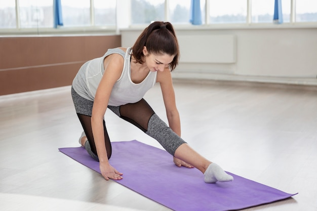 Young beautiful brunette woman practices yoga in the hall.