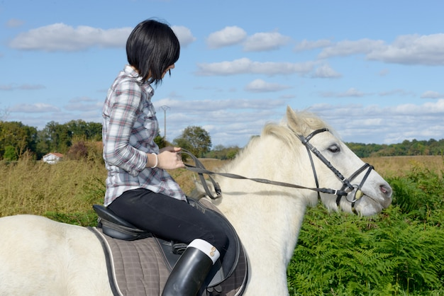 Young beautiful brunette woman riding horse