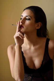 Young beautiful brunette woman smoking cigarette on yellow background.