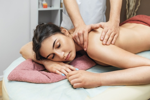 Young beautiful brunette woman in a spa salon is resting during a massage session in the trapezius muscles and cervical region