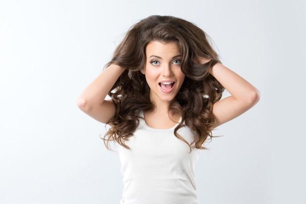若い美しいブルネットの女性は驚いた。驚き-女性は側に見て興奮しています。興奮の横て驚いた幸せな若い女。