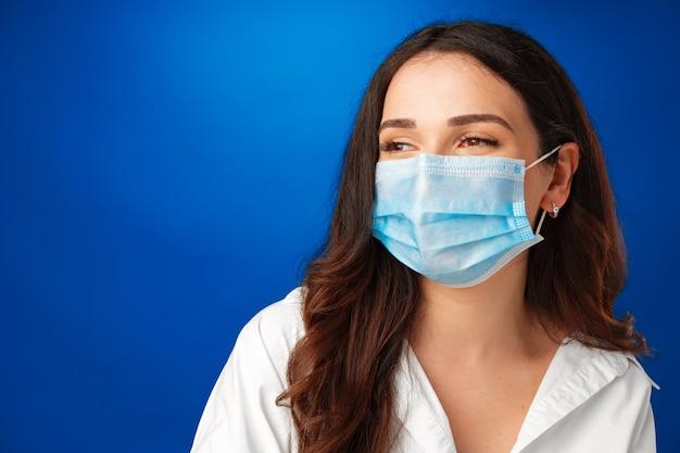 Молодая красивая брюнетка женщина в медицинской маске на синем фоне