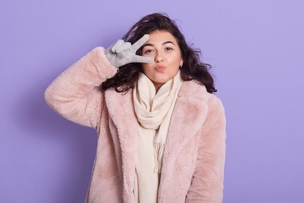 ピンクの冬の毛皮のコートを着て、幸せそうな顔で立っている若い美しいブルネットの女性