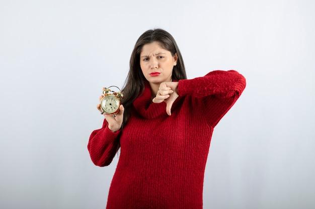 親指を下に表示する目覚まし時計を持つ若い美しいブルネットの女性。高品質の写真
