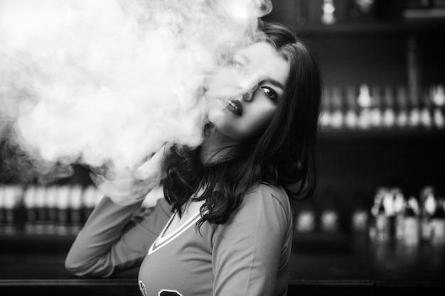 Молодая красивая брюнетка женщина с модным макияжем в баре с паром от электронной сигареты