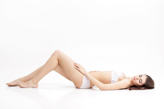 白い下着で細長い脚を持つ若い美しいブルネットの女性は、孤立した背中に横たわっています