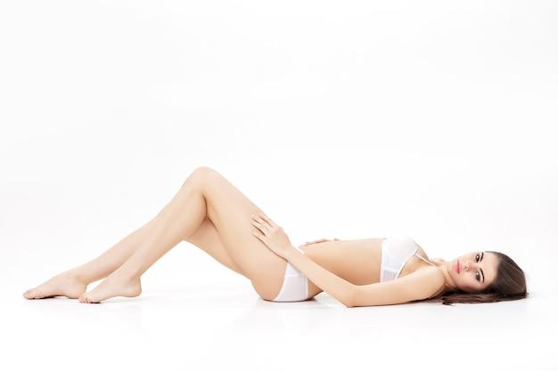 白い下着で細長い脚を持つ若い美しいブルネットの女性