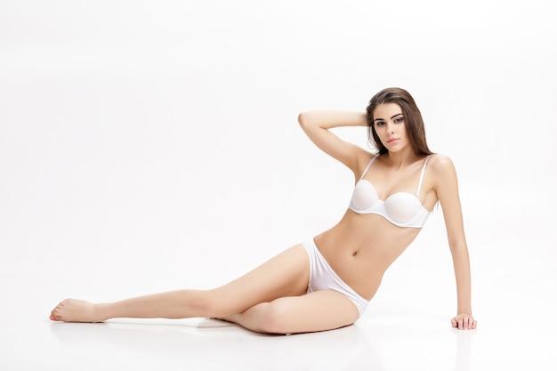 孤立した床に座っている白いlunderwearの完璧なボディを持つ若い美しいブルネットの女性