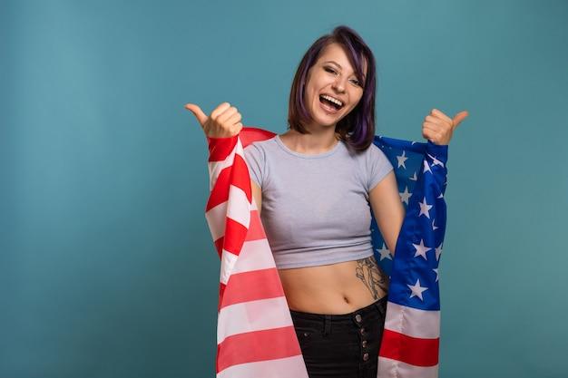 Молодая красивая брюнетка женщина с фиолетовыми крашеными волосами и пирсингом с полосами американских звезд флаг сша в ее руках на синем фоне