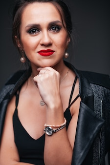 黒い背景に赤い唇を持つ若い美しいブルネットの女性