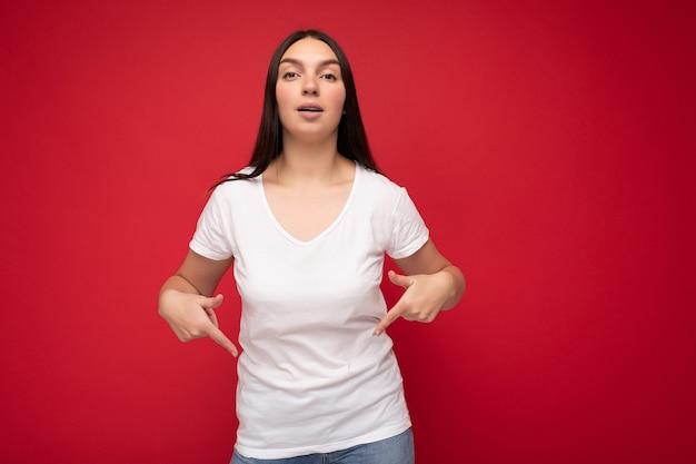 이랑 캐주얼 흰색 티셔츠를 입고 빈 공간에서 손가락을 가리키는 복사 공간 배경 벽에 고립 된 성실한 감정을 가진 젊은 아름 다운 갈색 머리 여자. 긍정적 인 개념.
