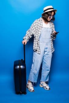 若い美しいブルネットは分離された彼女のスーツケースの横にテキストメッセージを書き込みます