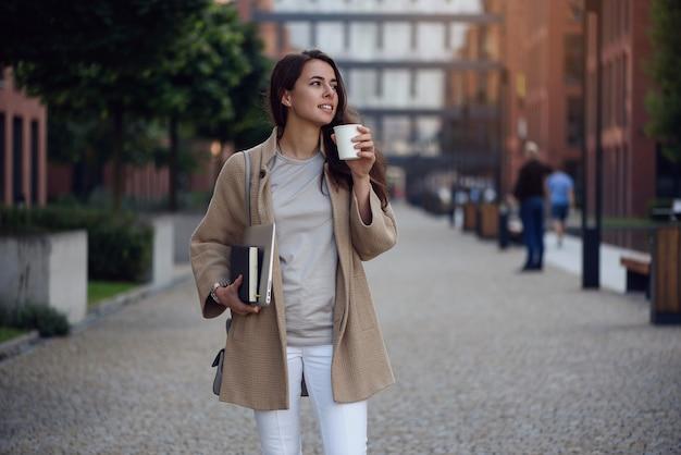 コーヒーの昼休みのカップとオフィスセンターの近くのカジュアルな服で若い美しいビジネスウーマン