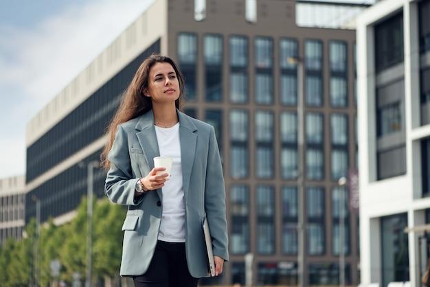 커피 점심 시간과 함께 사무실 센터 근처 캐주얼 옷을 입은 젊은 아름다운 비즈니스 여성