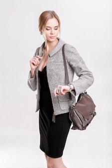 검은 드레스, 재킷과 지갑에 젊은 아름 다운 비즈니스 여자 금발 회색 배경에 그녀의 시계를 살펴 봅니다. 소녀는 시간에 늦었다