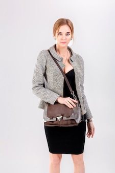 Молодая красивая бизнес-леди блондинка в черном платье, куртке и кошельке на сером фоне