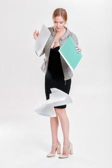 黒のドレスで金髪の若い美しいビジネス女性、ジャケットは灰色の背景に書類のフォルダーを落としました
