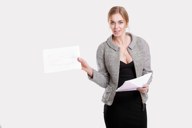 Молодая красивая бизнес-леди блондинка в черном платье, пиджак держит папку с бумагами и улыбается на сером фоне