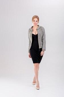 Молодая красивая бизнес-леди блондинка в черном платье, куртке на сером фоне