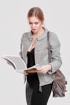 黒のドレス、灰色の背景で雑誌を読んでジャケットの若い美しいビジネス女性金髪