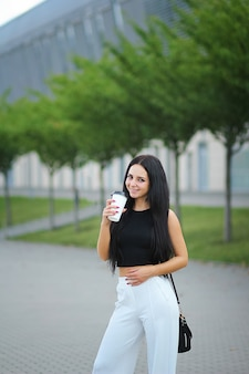 Young beautiful business woman drinks coffee near beside office building