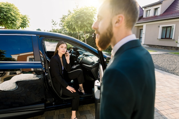 Young beautiful business woman getting out the front door of her car. driver or business partner helping woman to get out of the car