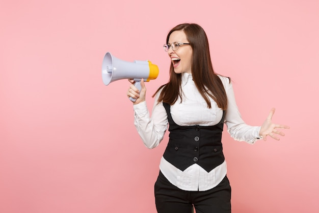 Young beautiful business woman in glasses screaming holding megaphone spreading hands isolated on pastel pink background. lady boss. achievement career wealth concept. copy space for advertisement.
