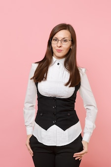 Молодая красивая деловая женщина в белой рубашке, костюме и очках, держа руки в карманах, изолированных на пастельно-розовом фоне. леди босс. концепция богатства карьеры достижения. скопируйте место для рекламы.