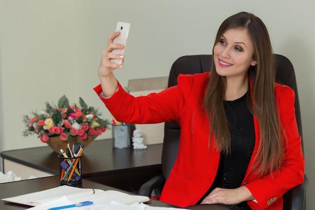 Молодая красивая бизнес-леди делает селфи в офисе.