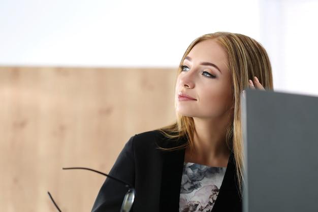 Молодая красивая деловая женщина сидит на своем рабочем месте и о чем-то мечтает