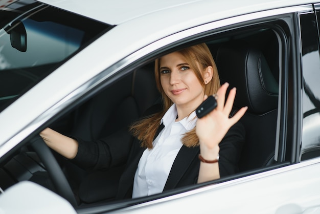 Young beautiful business woman sitting in her car