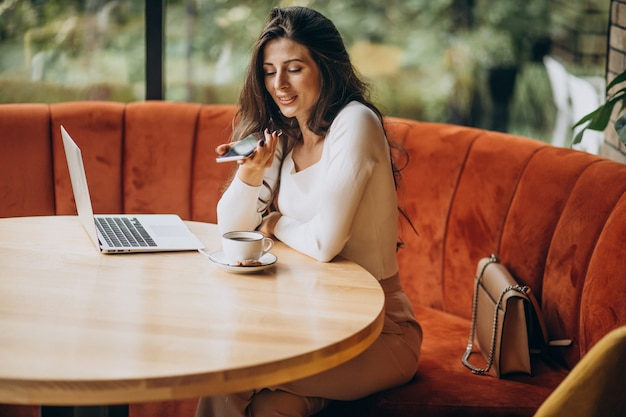 Young beautiful business woman working on computer in a cafe