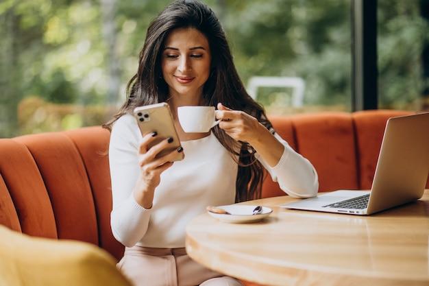 Молодая красивая деловая женщина, работающая на компьютере в кафе